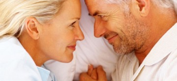 Closeup of a smiling romantic mature couple holding hands on bed