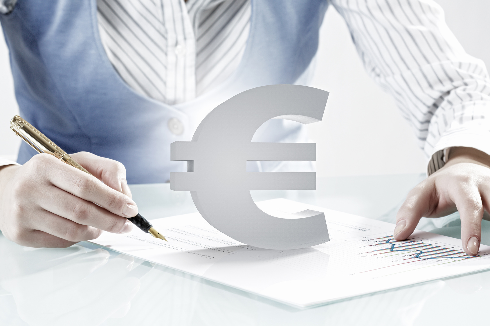 Close view of businesswoman writing with pen and currency euro sign
